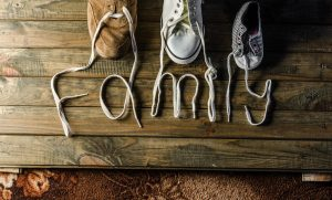 """A trio of shoes with their laces extended. The laces intertwine to read """"family""""."""