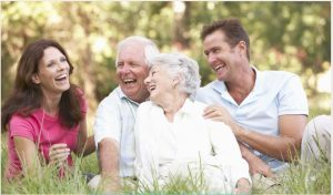 An older couple sit in a field with their adult children
