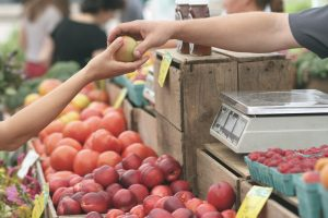 A customer buys an apple at a farmers market
